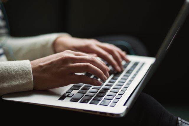 Tangenbord på en laptop och händer som skriver